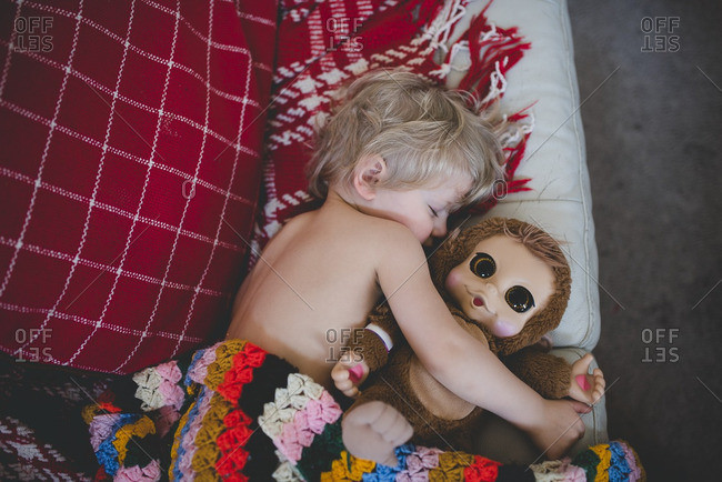 Boy sleeping with a stuffed monkey