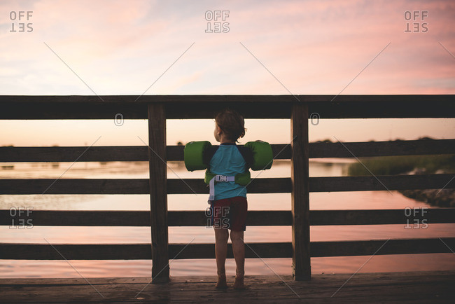 Boy standing on a wood pier wearing floaties