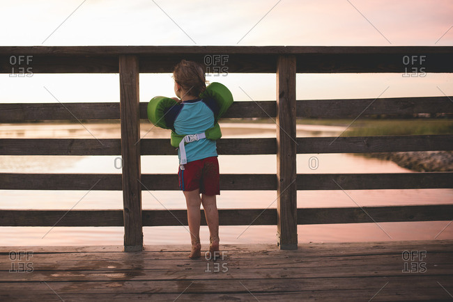 Boy standing on a pier wearing floaties