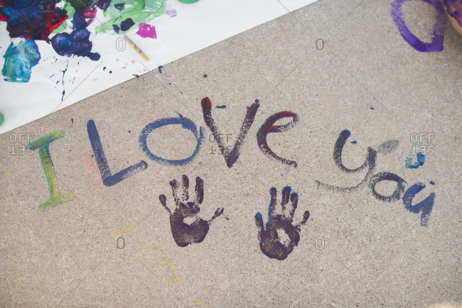 Handprints and the phrase 'I Love You' stamped in paint on a sidewalk