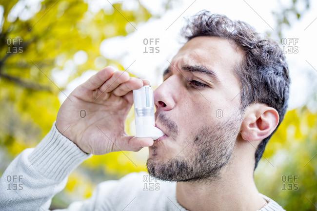 Young man using asthma inhaler, close-up