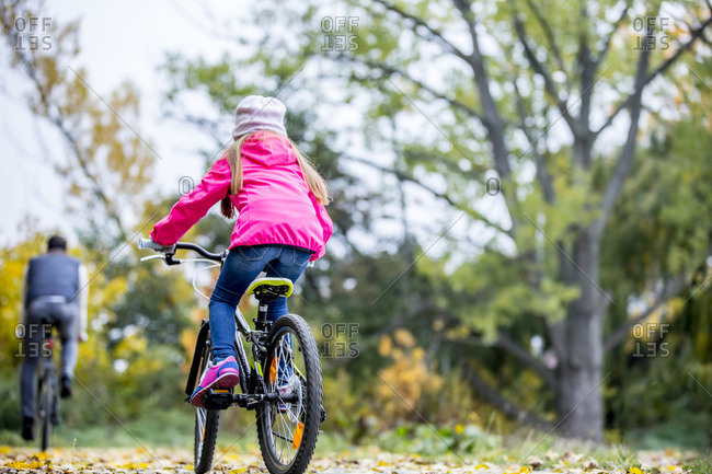 Rear view of girl cycling in autumn