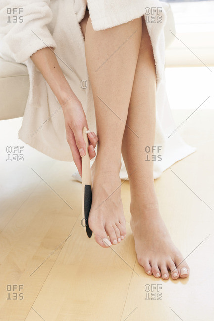 Young woman using pedicure equipment