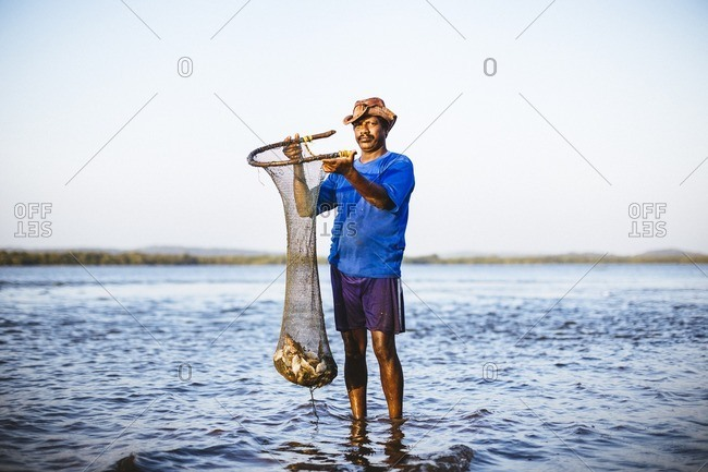 Panjim, India - January 11, 2016: A fisherman holds up his daily catch on the river in Panjim, India