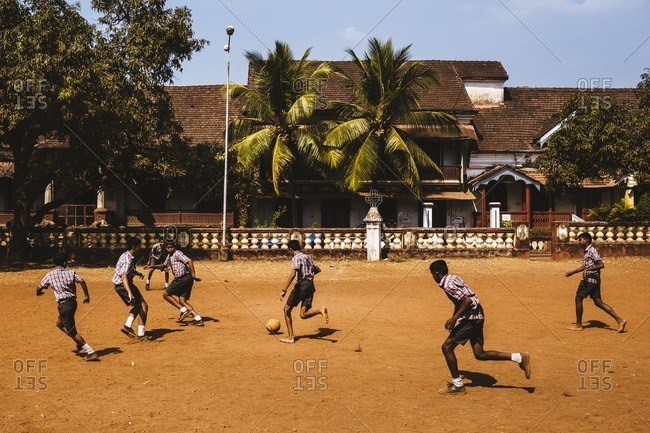 Margao, India - January 14, 2016: School children play a game of football with an old Portuguese mansion in the background in Margao, India