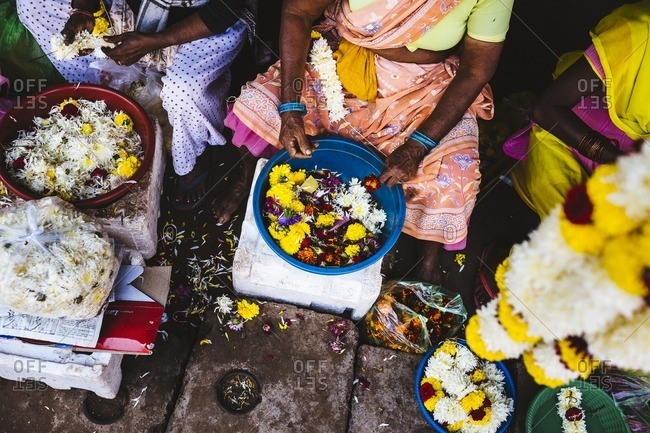 Women lace flowers on strings at the Margao market in southern Goa, India