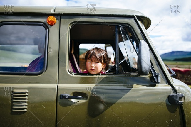 Mongolia - July 11, 2016: A young girl in an old Russian van in northern Mongolia