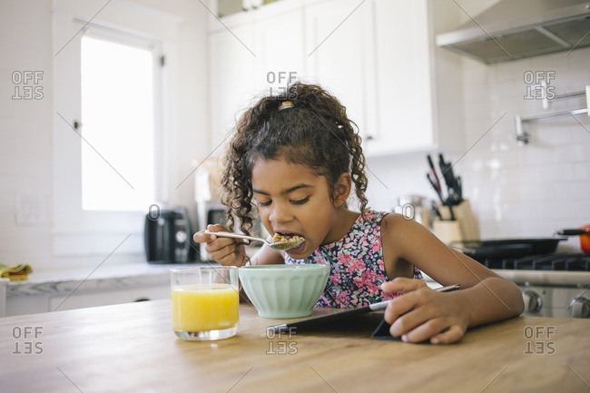 Girl eating cereal using tablet