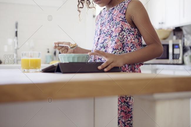 Girl eating breakfast using tablet