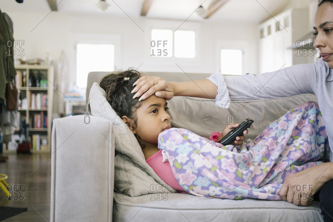 Mom with sick girl on couch