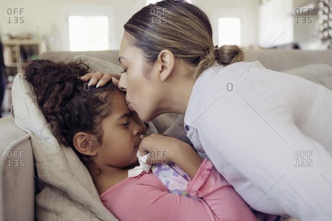 Mom kissing a sick girl