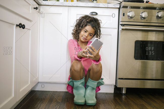 Hispanic girl using phone in kitchen