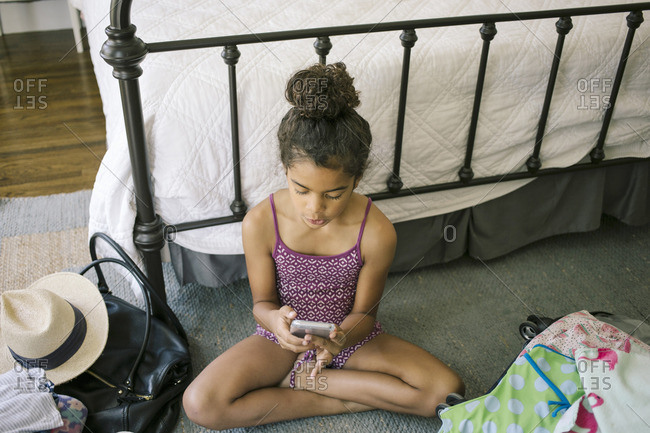 Girl on bedroom floor with phone