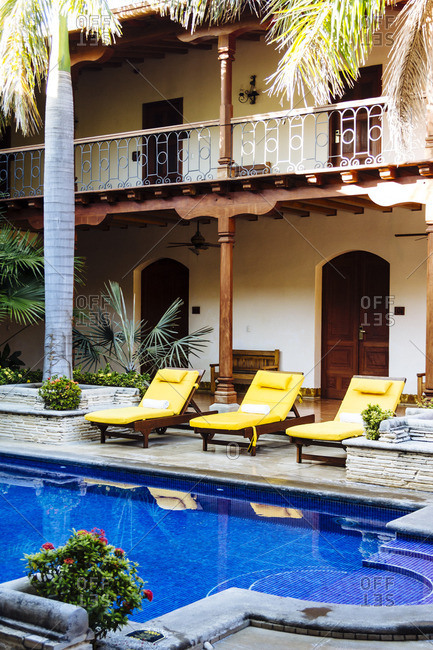 Lounge chairs by swimming pool at luxury hotel