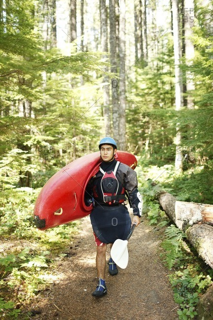 Young man carrying kayak while walking in forest