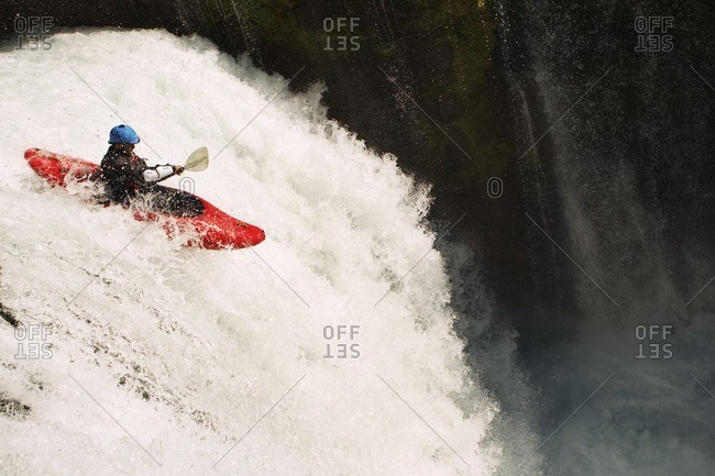 Man kayaking on waterfall on river