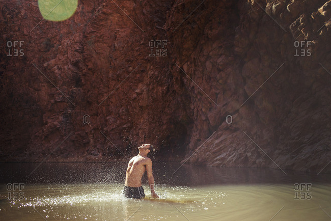 Shirtless man standing and shouting in lake by mountain