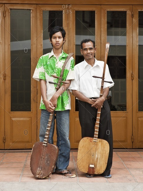 Teacher and student standing and holding traditional Cambodian lutes