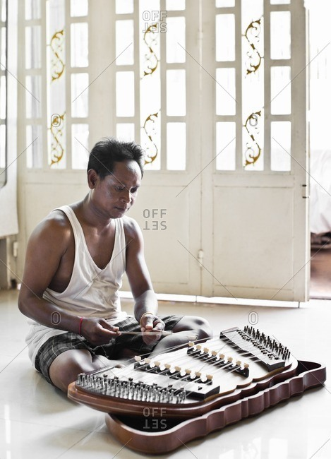 Cambodian instrument maker sitting on the floor playing a traditional khim tuch