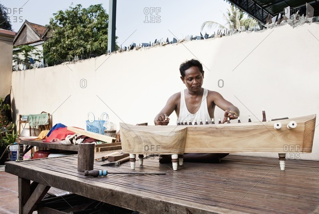 Cambodian instrument maker building a traditional takhe at his home