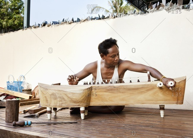 Instrument maker putting together a traditional Cambodian takhe