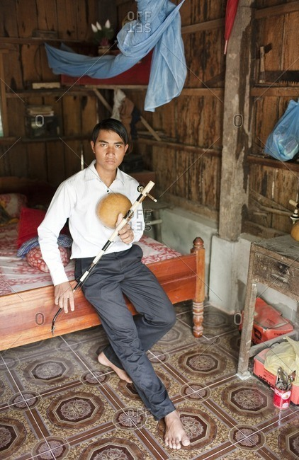Cambodia - February 16, 2009: Young man sitting on a bed holding a traditional Cambodian instrument