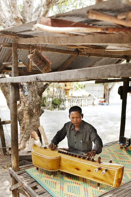 Cambodia - February 16, 2009: Cambodian musician playing a traditional takhe under a shelter