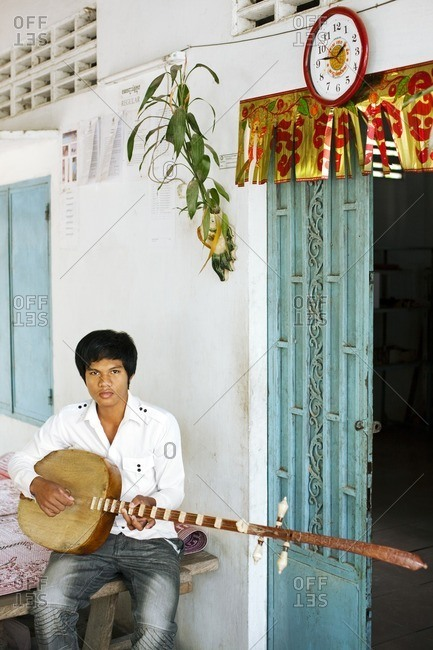 Cambodia - February 16, 2009: Young man holding a traditional Cambodian stringed instrument