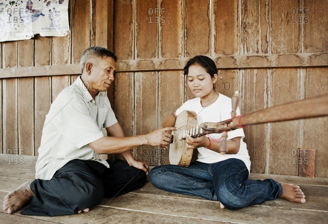 Cambodia - February 20, 2009: Musician teaching a student to play a traditional Cambodian instrument