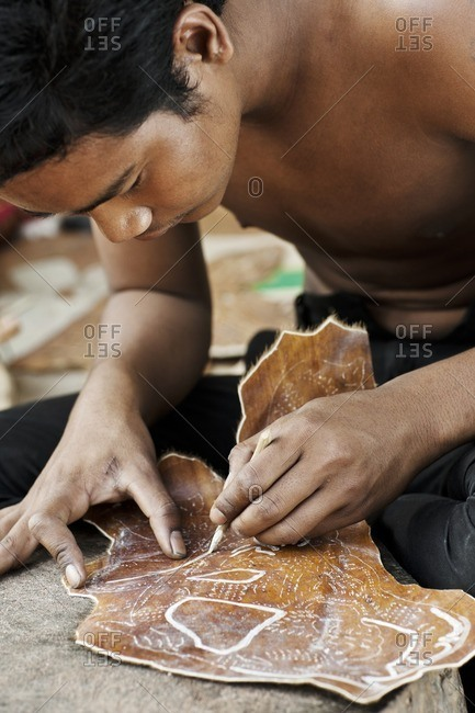 Cambodia - February 21, 2009: Man carving animal hide for traditional Cambodian shadow puppets