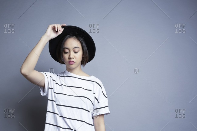Young woman in a striped t-shirt holding a hat on her head
