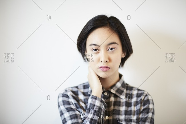Young woman in a plaid shirt touching her face
