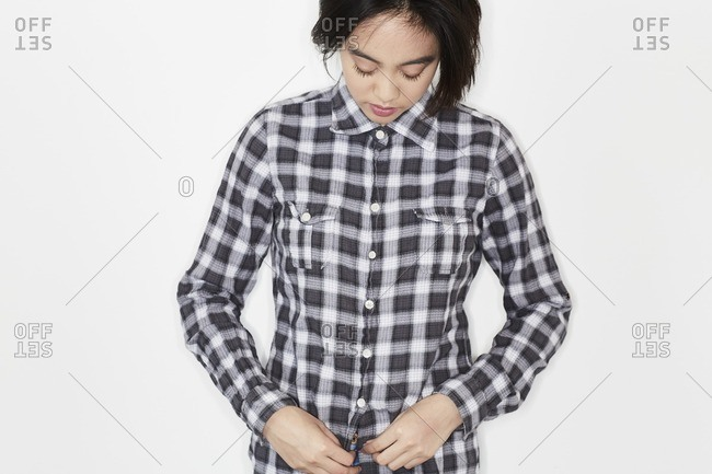 Young woman buttoning a black and white plaid shirt