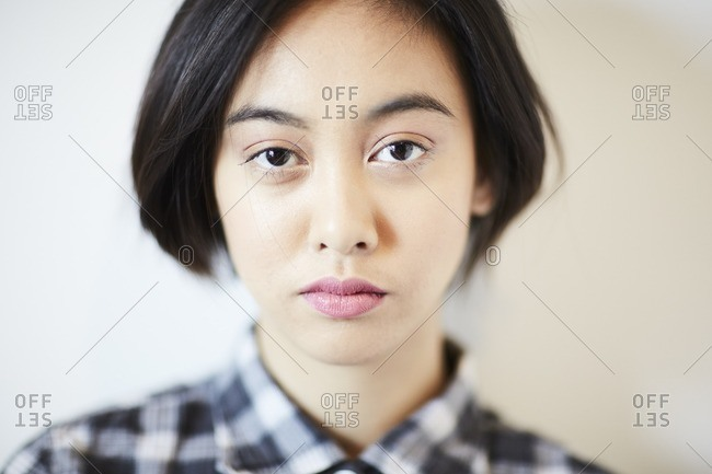 Young woman in a plaid shirt gazing at the camera