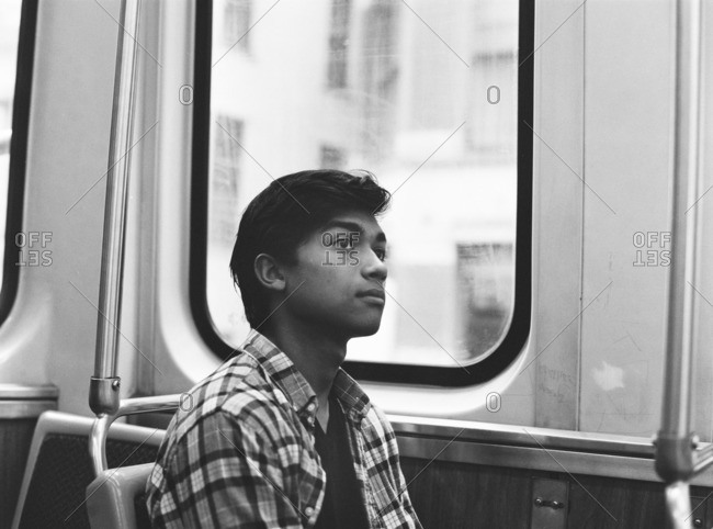 Young man sitting thoughtfully in a subway car