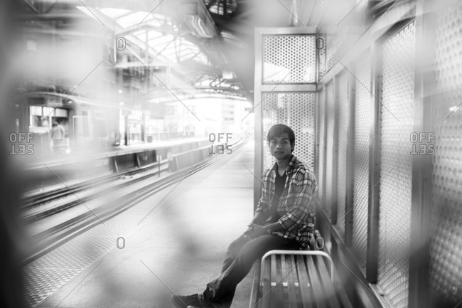 Young man sitting on a bench in a subway station