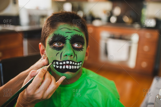 Boy having his face painted green for a Halloween costume