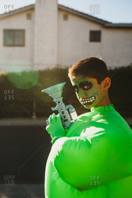 Boy posing in a green monster costume with a gun