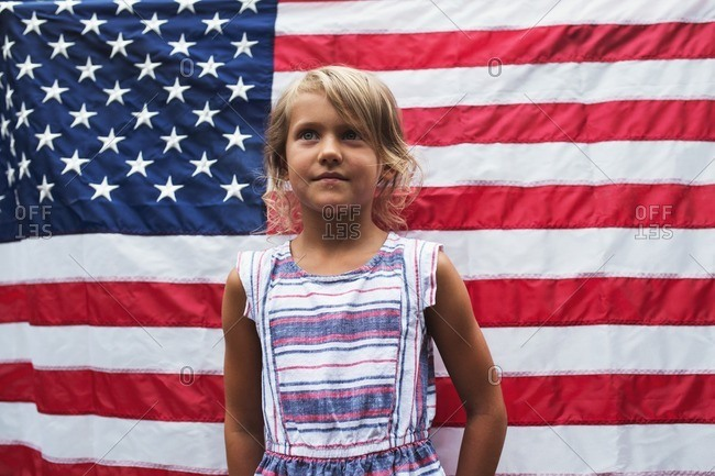 Young girl standing in front of the American flag