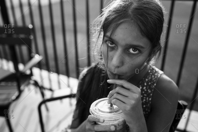 Tween girl drinking out of a straw