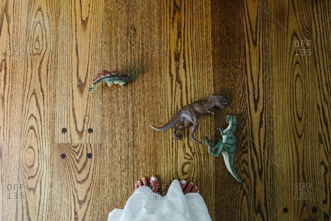 A woman with pedicured feet standing next to a group of toy dinosaurs on a wood floor