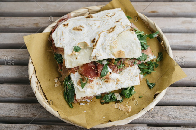 Freshly prepared piadina with meat and greens on Italian flatbread