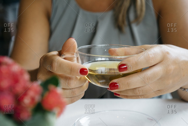Close-up of a woman holding a glass of herbal tea