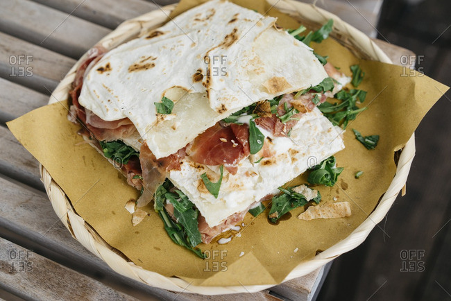 Piadina with meat and greens on Italian flatbread served on a plate