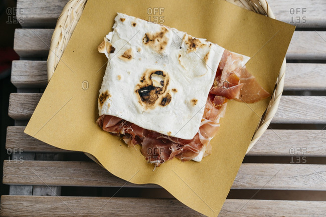 Freshly prepared piadina with prosciutto on Italian flatbread