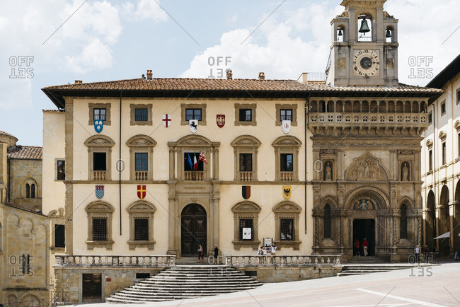 July 27, 2016: Exterior of historic building with bell tower in the Piazza Grande in Arezzo, Italy