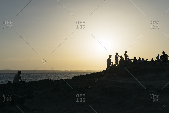Silhouette of people watching the sunset on the island of Formentera, Spain