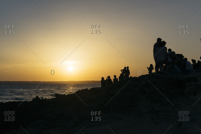Silhouette of many people watching the sunset on the island of Formentera, Spain