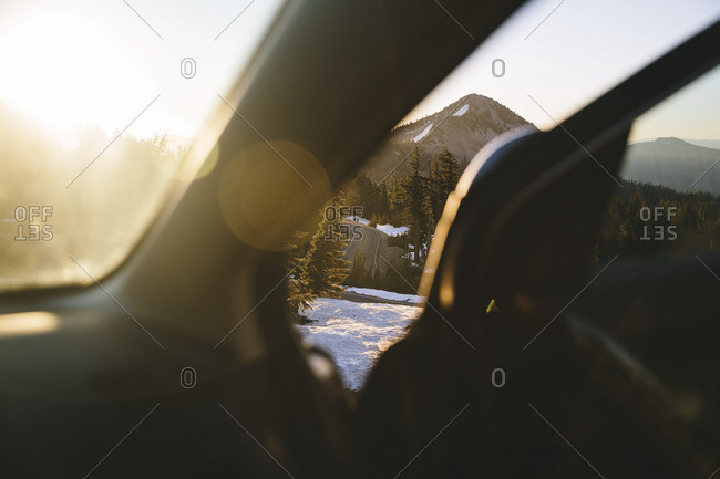 Mountain, road, and snow covered ground seen through the open door of a car