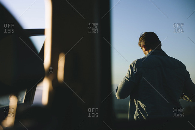 Man standing outside of a car window